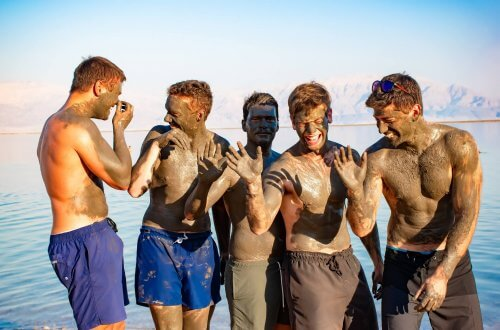 People take mud baths at the dead sea and having fun with mud